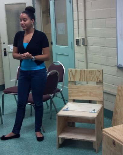 URI Honors class presenter discussing how the box becomes a chair becomes a table becomes a stool.